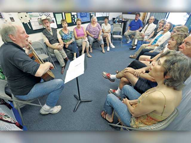 "Jim Scott, left, leads a group in a sing-along with the Pete Seeger folk song ""If I Had a Hammer"" during a folk song festival held at Unitarian Universalists of Santa Clarita Chalice Center in Newhall on Saturday."
