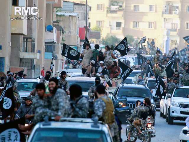 This undated file photo posted by the Raqqa Media Center, a Syrian opposition group, on June 30, which has been verified and is consistent with other AP reporting, shows fighters from extremist Islamic State group during a parade in Raqqa, Syria.