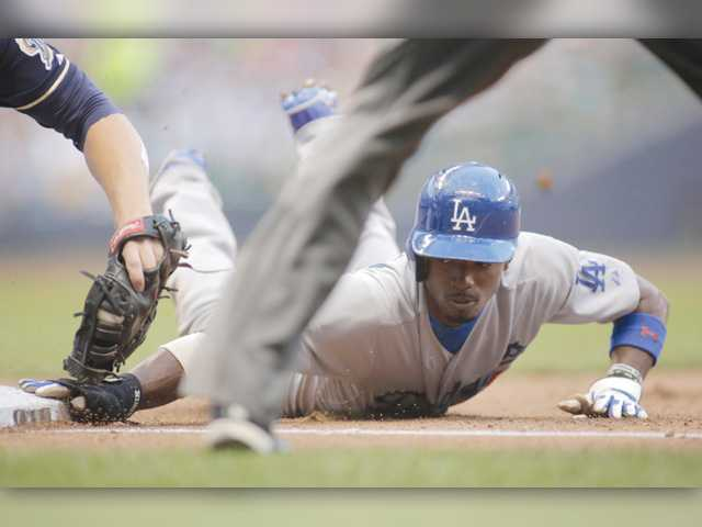 LA's Dee Gordon, right, is called safe against the Milwaukee Brewers during Saturday's game in Milwaukee.