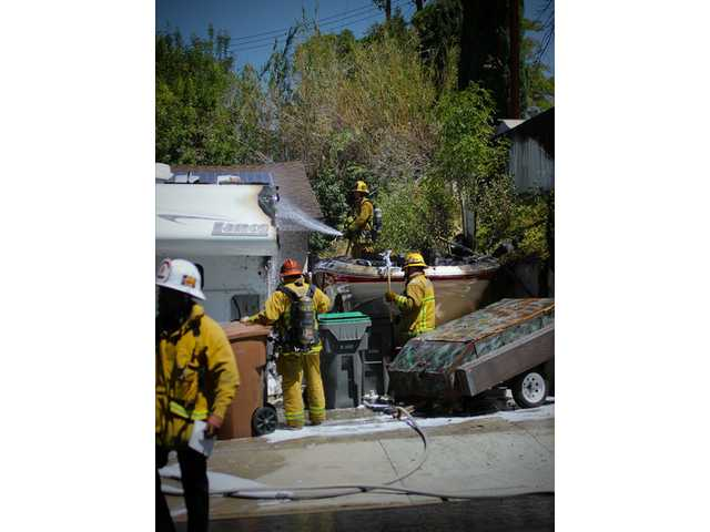 Firefighters mop up after a boat fire in the driveway of a home on Delight Street in Canyon Country on Tuesday. Signal photo by Austin Dave