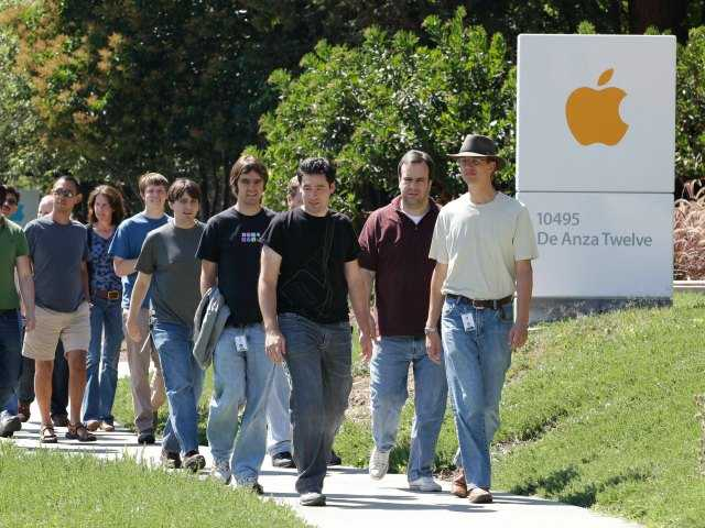 In this Aug. 25, 2011 file photo, Apple employees walk between buildings at Apple headquarters in Cupertino, Calif. A breakdown released Tuesday, Aug. 12, 2014 by Apple Inc. showed 54 percent of the company's technology jobs in the U.S. are handled by whites and another 23 percent by Asians. (AP Photo/Paul Sakuma, File)