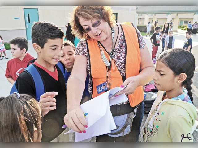 Students gather around safety superintendent Susan Makishima, center, as she matches their names with their new classrooms on the first day of school at Dr. J. Michael McGrath Elementary School in Newhall on Tuesday. Signal photo by Dan Watson.