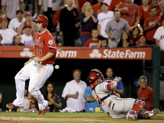 Los Angeles Angels' David Freese, left, scores past Philadelphia Phillies catcher Carlos Ruiz on a hit by Chris Iannetta during the sixth inning of Tuesday's game in Anaehim.