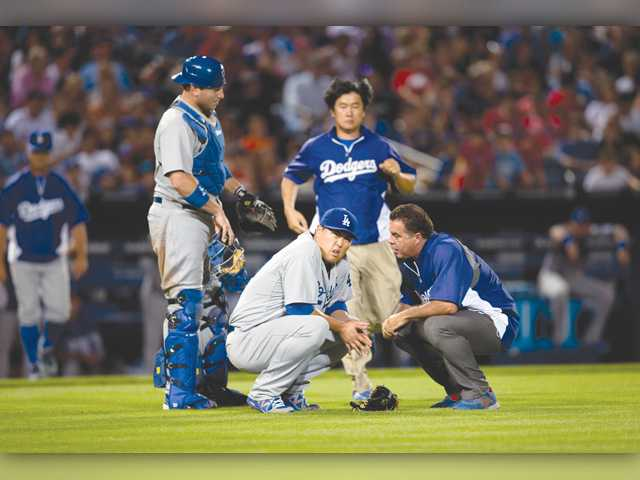 A member of the Los Angeles training staff talks to injured starting pitcher Hyun-Jin Ryu (99) as catcher A.J. Ellis looks on during Wednesday's game in Atlanta.
