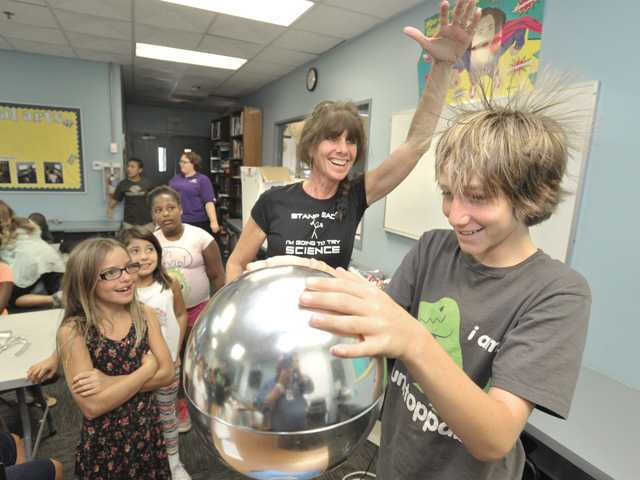 Vicki White the Science Lady, center, demonstrates the effects of the Van de Graaff electrostatic generator as it makes Wylnd Heathman's hair stand on end during an electric circuitry science class presented at the Boys & Girls Club of Santa Clarita Valley. Signal photo by Dan Watson