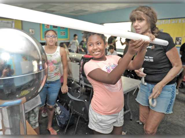 The Science Lady Vicki White, right, looks on as Chya Williams, 10, holds a fluorescent light bulb as it lights from the static electricity produced by the Van de Graaff electrostatic generator. Signal photo by Dan Watson