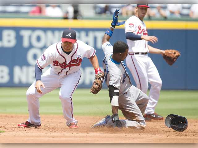 Los Angeles' Dee Gordon (9) steals second base as Atlanta Braves second baseman Tommy La Stella (7) applies the late tag in Thursday's game in Atlanta.