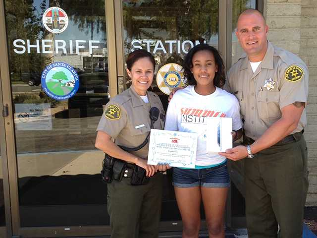 Essay contest winner Brianna Price, 13, center, stands with Santa Clarita Valley Sheriff's Station deputies after receiving her iPad Mini tablet.
