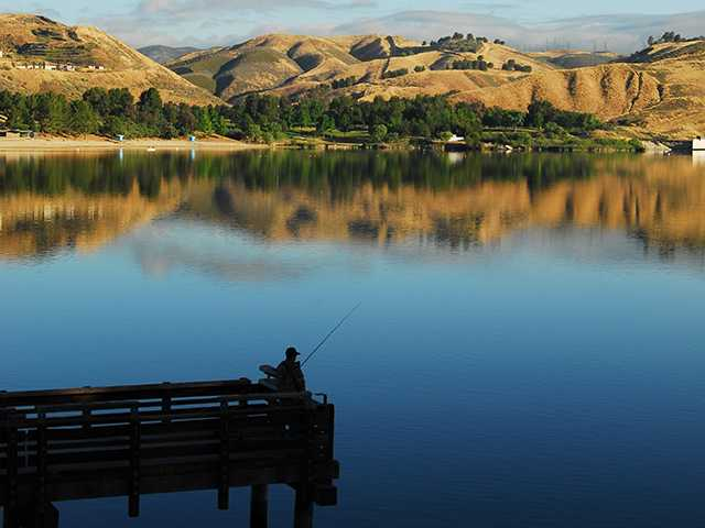 The surrounding mountains reflect off the still surface of the water at Castaic Lake. Gongping Zhang / Courtesy photo