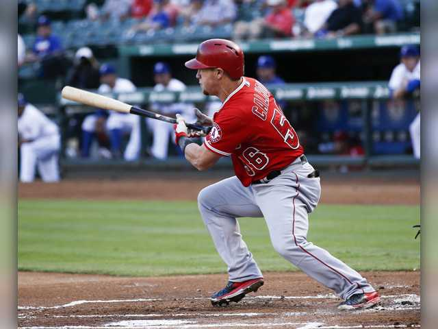 Los Angeles Angels' Kole Calhoun (56) follows through for a single against the Texas Rangers during the first inning of a Friday's in Arlington, Texas.