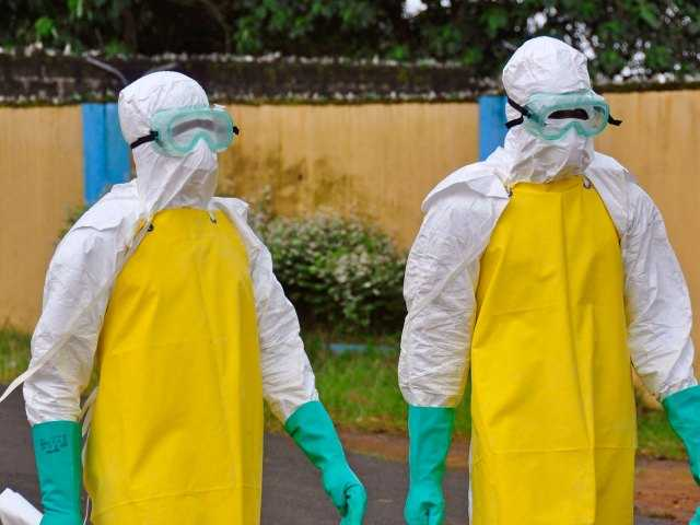 Health workers wearing protective gear go to remove the body of a person who is believed to have died after contracting the Ebola virus in the city of Monrovia, Liberia, Saturday.