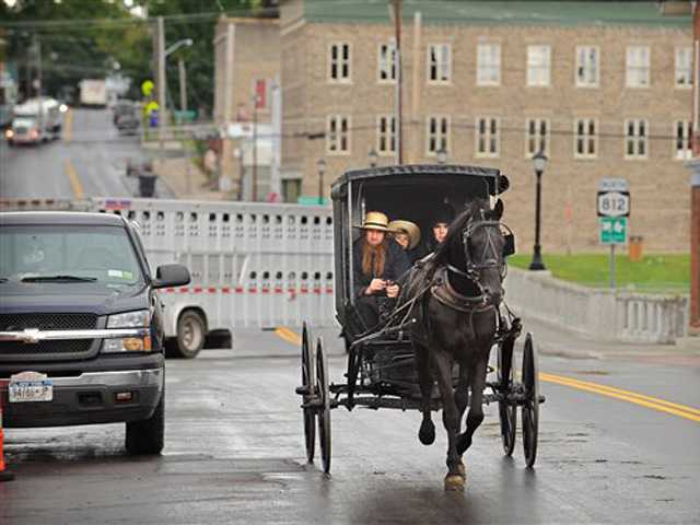 An Amish family rides along Route 812 in Heuvelton, N.Y., near the command center at the Heuvelton Volunteer Fire Department on Friday.