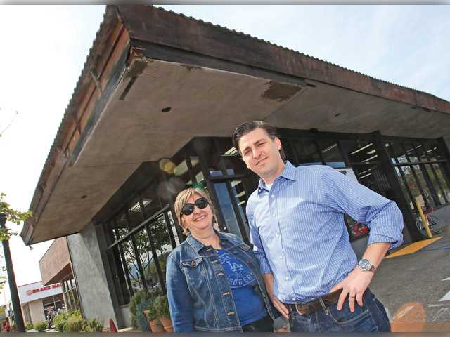 Mary Anne Amitin and her son Aaron stand in front of the building that previously housed Billy's Boardshop until 2013.