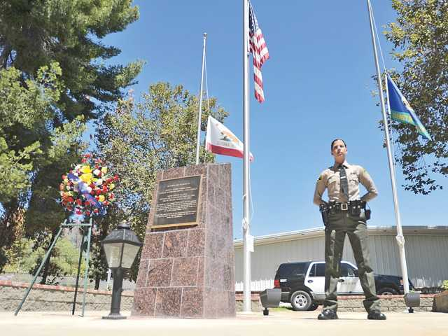 A deputy stands watch at a 24-hour vigil at Pitchess Detention Center on Saturday in memory of Deputy Shayne York, who was killed in a 1997 armed robbery at a beauty salon in Buena Park. Signal photo by Katharine Lotze
