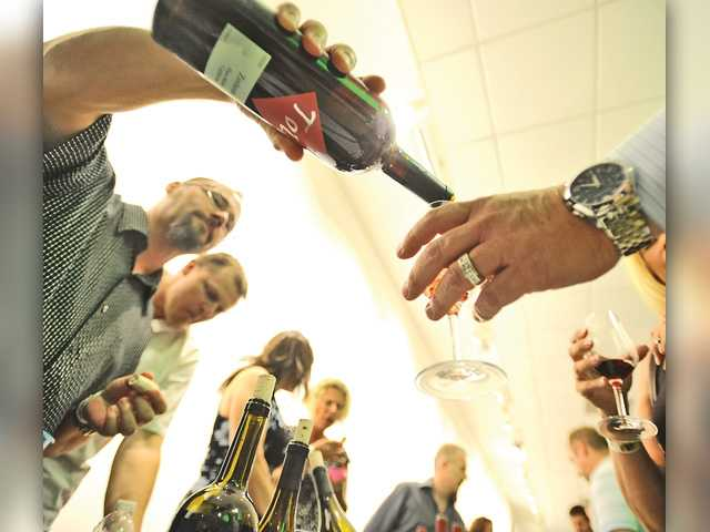 Frank Fazzio pours a sample of Tolo Cellars wines for a guest at the annual Vine 2 Wine Classic at CalArts on Saturday. Katharine Lotze/The Signal