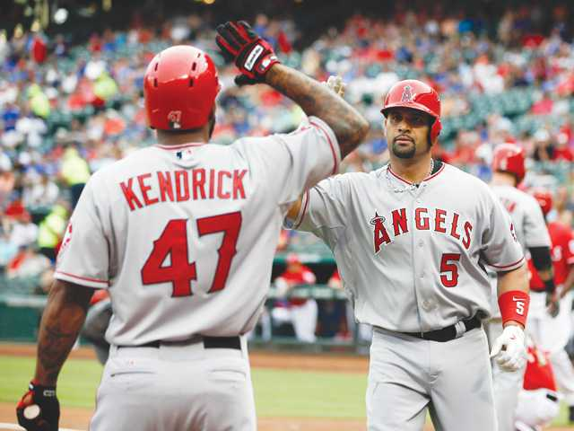 The Angels' Albert Pujols (5) is greeted by Howie Kendrick (47) after his solo homer on Saturday in Arlington, Texas.