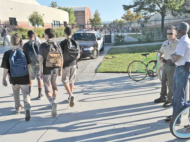 Valencia High School students arrive for class Monday morning while sheriff's deputies observe their arrival following online threats. Signal photo by Katharine Lotze