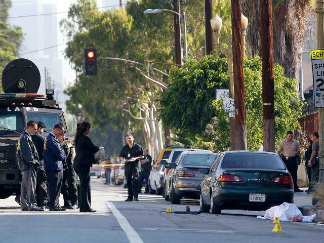 Police investigators check the scene after an early morning police chase in Los Angeles on Monday, Aug. 18, 2014. (AP Photo/Nick Ut)