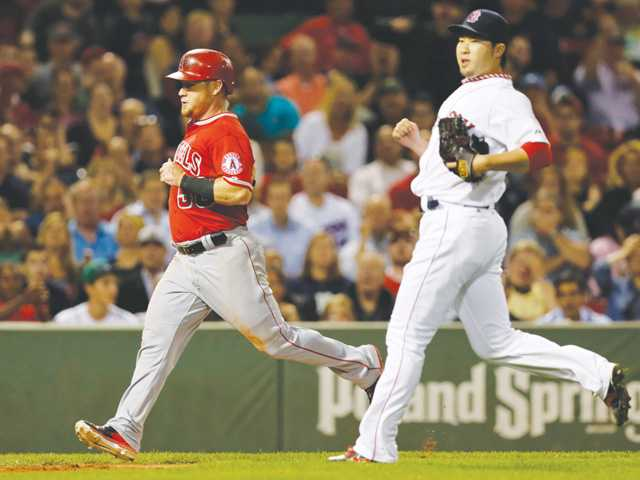 Boston Red Sox relief pitcher Junichi Tazawa, right, follows Los Angeles Angels Kole Calhoun at Fenway Park in Boston on Monday.