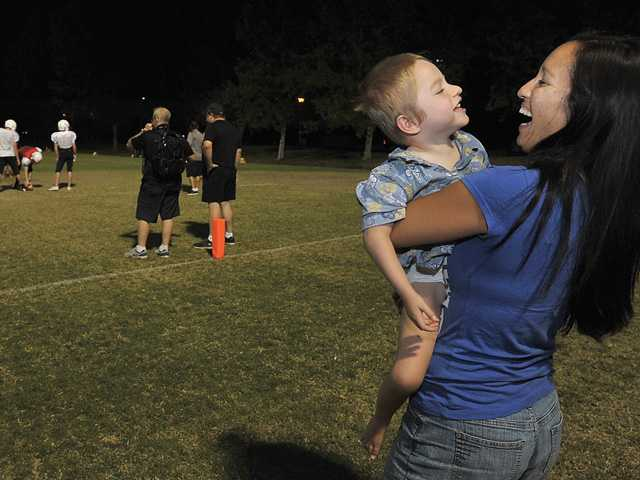 It's a common sight to see Kendra Moss, wife of Santa Clarita Christian football coach Garrick Moss, with their youngest son, Blake, during a football practice. It's often how the family spends its time together.