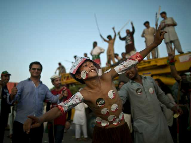 A young supporter of Pakistani cricketer-turned-politician Imran Khan, his body decorated with stickers showing Khan, dances with others during a protest in Islamabad, Pakistan, Tuesday, Aug. 19, 2014. (AP Photo/Muhammed Muheisen)