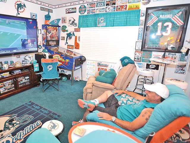 Stuart Thompson sits in his man cave decked out with Miami Dolphins memorabilia. Signal photo by Katharine Lotze