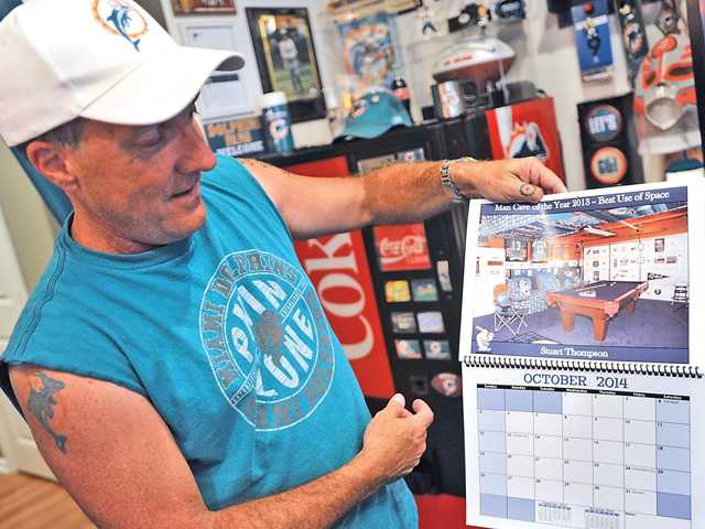 "Stuart Thompson shows off a calendar called ""Man Cave of the Year 2014,"" where he won best use of space for his original man cave in his old house. Signal photo by Katharine Lotze"