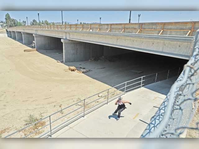 A skater passes under the McBean Parkway Bridge on the bike path Wednesday. Signal photo by Dan Watson