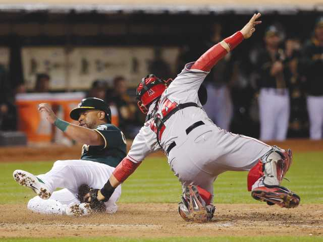 Oakland' Alberto Callaspo, left, scores past Angels catcher Hank Conger in Friday's game in Oakland.