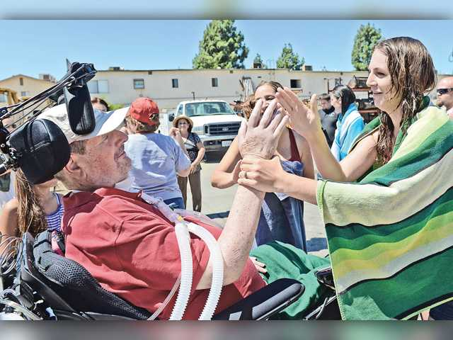 Caretaker Liz Kerr gives a high five to Cary Dermer, an SCV resident who has lived with ALS for 11 years. His five caregivers took the ice bucket challenge at AV Equipment Rentals in Newhall Saturday as ice water was dumped on them from a skip loader. Photo For The Signal/Jayne Kamin-Oncea