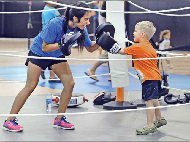 Rebeca Solorzano, left, spars with Zach Carlucci, 3, in a boxing ring set up in the gym at the Santa Clarita Sports Complex as one of the health and sports related events available for the attendees at the city of Santa Clarita Youth Sports & Healthy Families Festival on Saturday. Signal photo by Dan Watson