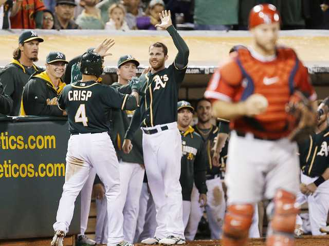 Oakland Athletics outfielder Coco Crisp (4) is congratulated after scoring on a wild pitch thrown by Los Angeles Angels' Joe Smith on Saturday in Oakland.