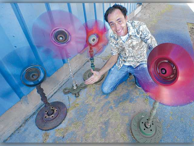 Artist Steve Jasik spins his wind fans made from recycled car parts — radiator fans, cam shafts and brake disks — displayed at German Autohaus body shop in Newhall. Signal photo by Dan Watson.