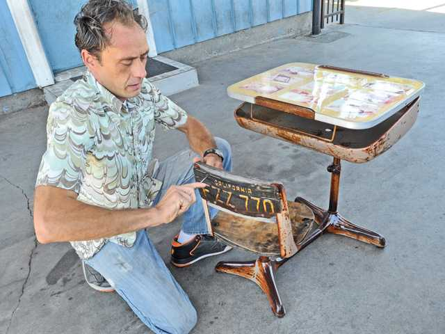 Artist Steve Jasik screws a car license plate to a 1960s school desk which has been clear coated to preserve the rusty patina of the desk at German Autohaus auto repair in Newhall. Signal photo by Dan Watson.
