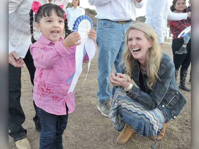 Carousel Ranch student Sophia Gittisarn, 3, left, holds up her 1st place riding ribbon presented by Jan Swartz, right, President of Princess Cruises after the riding demonstration by Carousel Ranch students at the 18th Annual Heart of the West fundraise. Signal photo by Dan Watson.