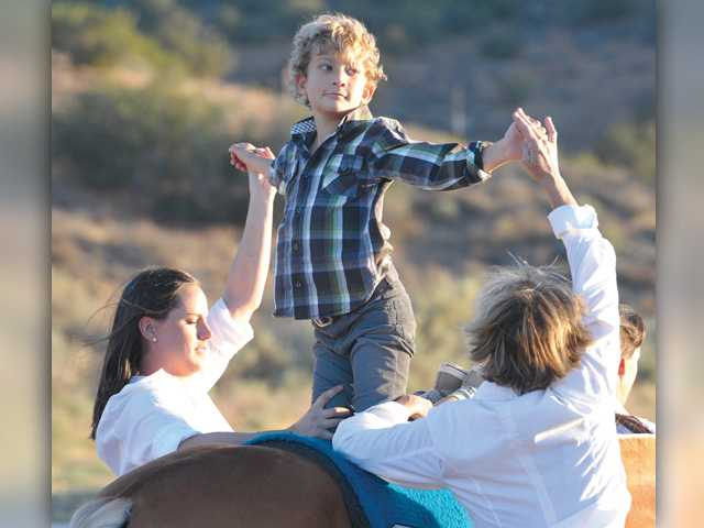 Carousel Ranch student Ronnie Riegler, 8, rides backwards on Mo as he demonstrates his riding skills.Signal photo by Dan Watson.
