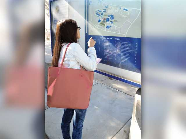 Cathy Huynh checks the map of the College of the Canyons Valencia campus on the first day of school for the fall semester Monday. Signal photo by Dan Watson