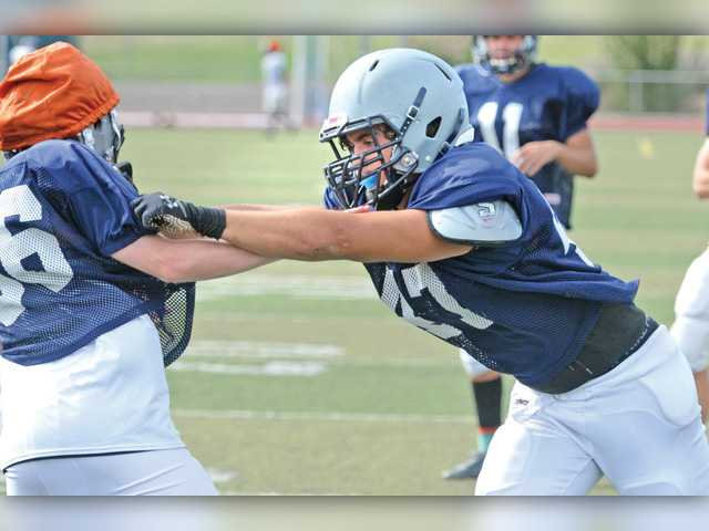 Senior linebacker Zach Gragas, right, runs drills with teammate Ashton Ferguson during practice at Saugus High School on Monday.