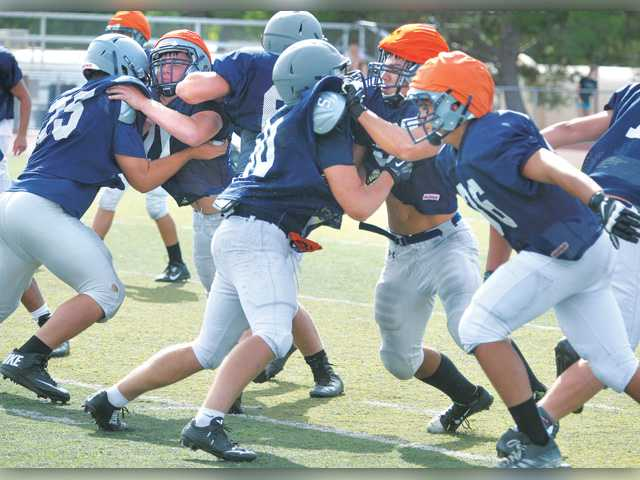 Saugus defenders rush the quarterback during a scrimmage at Saugus High School on Monday. Saugus returns just two starters from last year's defense.