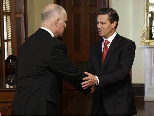California Gov. Jerry Brown greets Mexican President Enrique Pena Nieto after his arrival at the Leland Stanford Mansion in Sacramento on Tuesday.