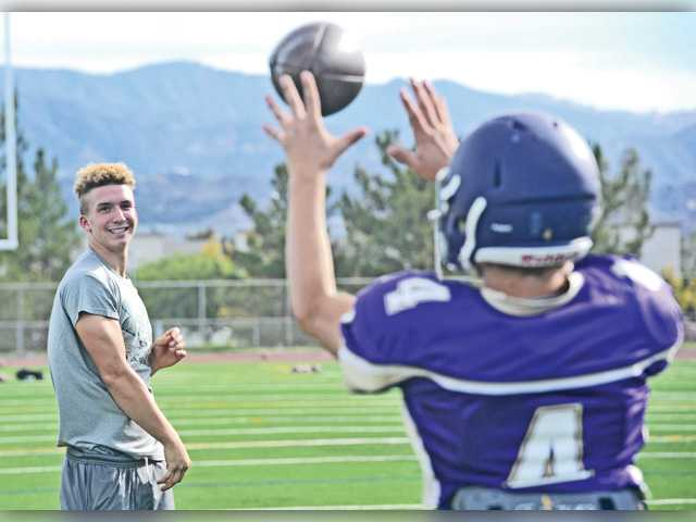Valencia's starting quarterback Cole Parkinson, left, throws with backup Kyle Prizer during practice on Monday at Valencia High.
