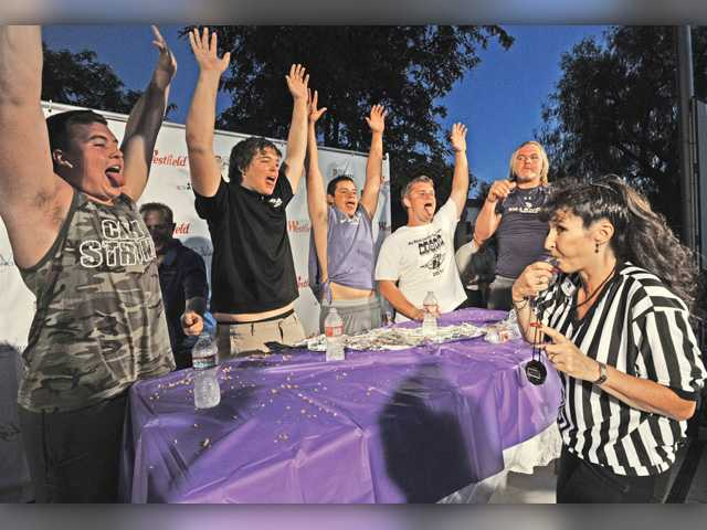 Members of the Valencia High School football team stick out their tongues to show they have no more food in their mouths as referee Christine Sexton blows the whistle after they finished their 4-foot burrito. Signal photo by Dan Watson.