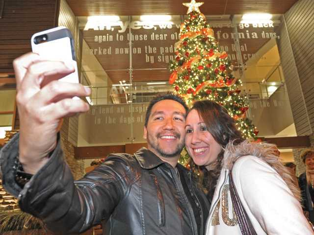 "In this Nov. 2013 photo, Arturo and Ana Dirzo take a photo in front of the 23-foot Christmas tree in front of the Old Town Newhall Library after last year's ""Light Up Main Street"" event."