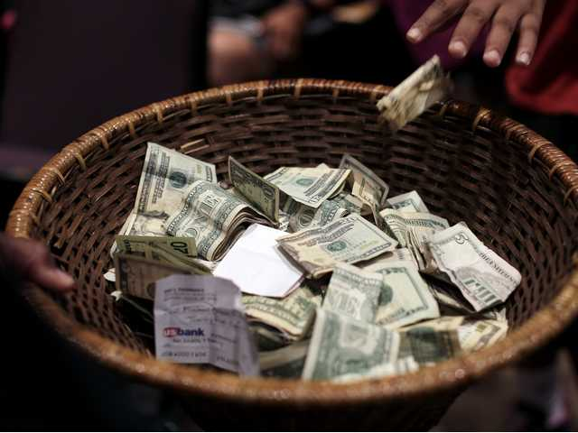 In this Aug. 9, 2014 photo people donate money for the family of Michael Brown during a rally in Ferguson, Mo.