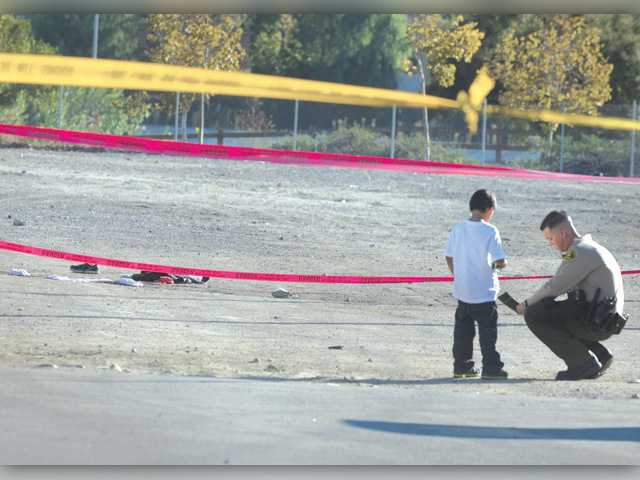A boy and a sheriff's deputy talk after a man was shot in the parking lot of a Canyon Country strip mall on Oct. 31, 2011. Signal file photo