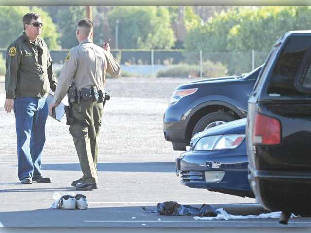 Sheriff's officials talk at the scene of a shooting in the parking lot of a Canyon Country strip mall where a man was gunned down on Oct. 31, 2011.