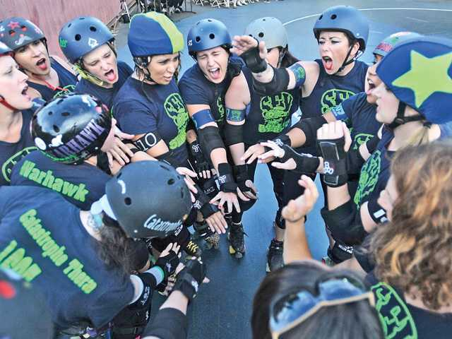 The San Fernando Valley Wipeouts women's roller derby team cheers before hitting the track for their game against the Bakersfield Unforgiven Roller Girls at The Lot in Sylmar. Signal photo by Katharine Lotze