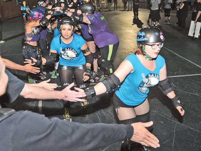 The Balboa Bandits high-five fans after the bout on a hot Saturday night last month. Signal photo by Katharine Lotze