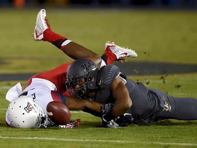 UCLA defensive back Anthony Jefferson, right, breaks up a pass to Arizona wide receiver Cayleb Jones on Saturday in Pasadena.