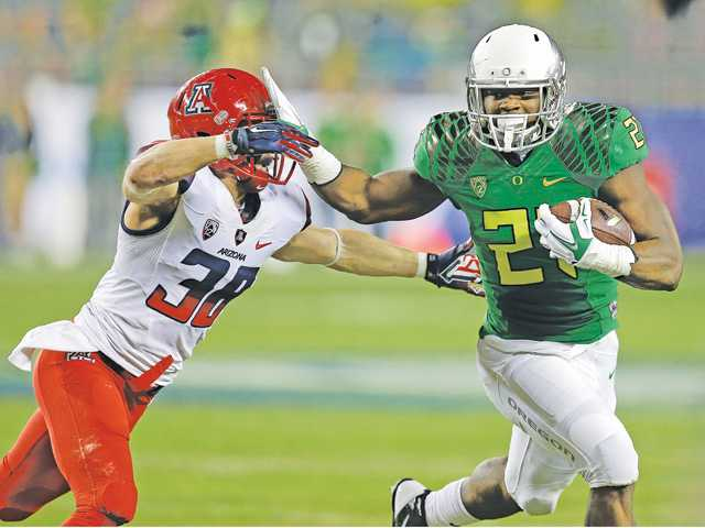 Oregon's Royce Freeman, right, evades the tackle of Arizona's Jared Tevis (38) during the Pac-12 Conference championship game on Friday in Santa Clara.